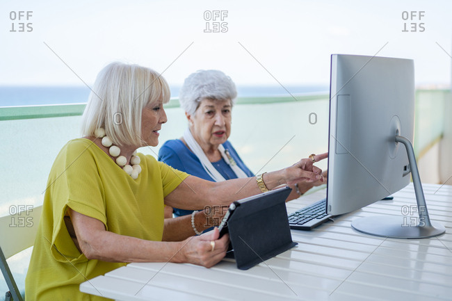 Stylish old friends browsing social media on tablet while sitting at table with computer on balcony on resort