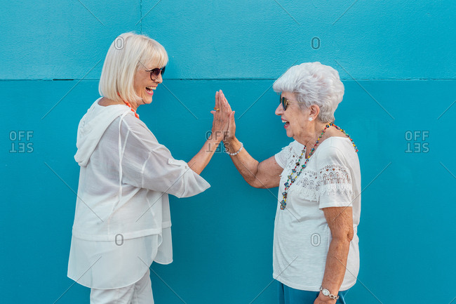 Side view laughing modern cheerful elderly grey-haired women in sunglasses rejoicing together giving high five looking at each other on blue background