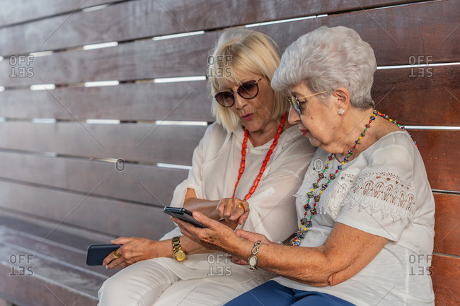 Confident fashionable cheerful grey-haired senior women in summer clothes and sunglasses speaking on large wood bench looking at each other