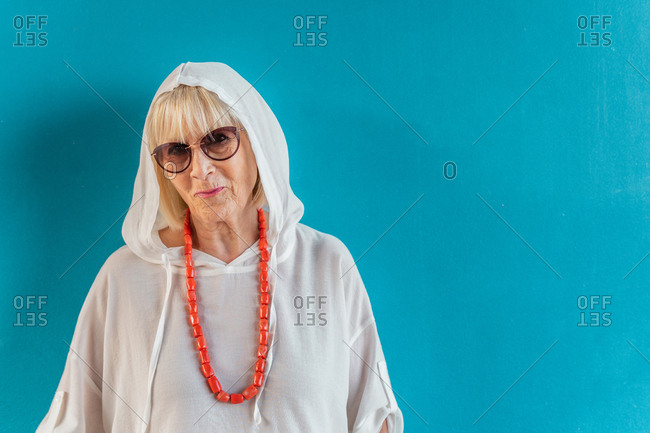Portrait of beautiful stylish white-haired senior woman with sunglasses in white shirt with hood on head and coral beads on blue wall background