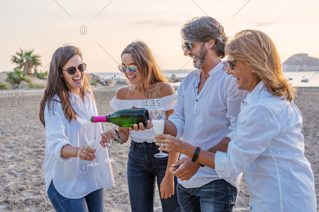 Cheerful mature parents and young daughters clinking glasses of wine and laughing while celebrating family reunion in evening on resort
