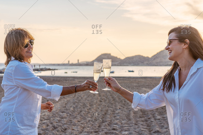 Mother and young daughter clinking glasses of wine and laughing while celebrating family reunion in evening on resort
