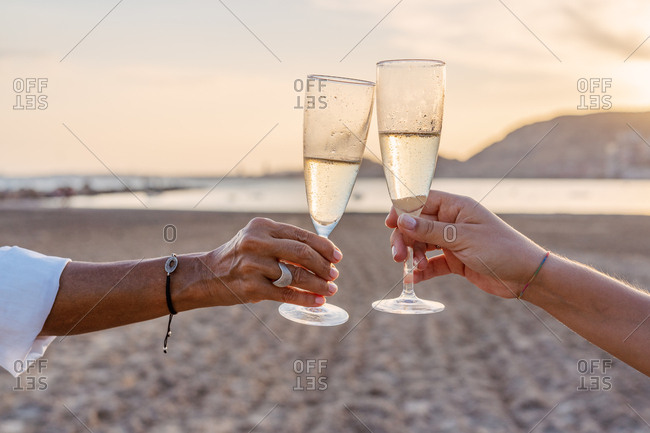 Unrecognizable mother and daughter clinking goblets of wine and proposing toast while celebrating family reunion on sandy beach in evening