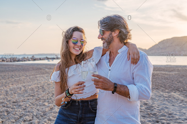 Mature man hugging young woman in cheek while proposing toast and celebrating family reunion on sandy beach during dusk on resort