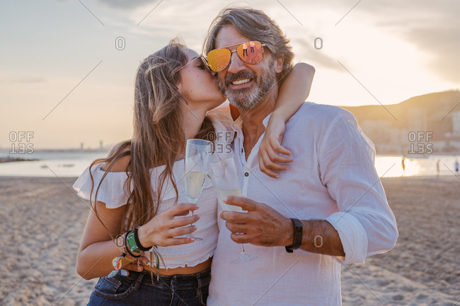 Mature man hugging and kissing young woman in cheek while proposing toast and celebrating family reunion on sandy beach during dusk on resort