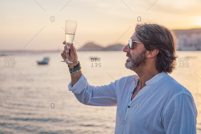 Side view of bearded mature man enjoying wine while standing against sea and sundown sky on resort