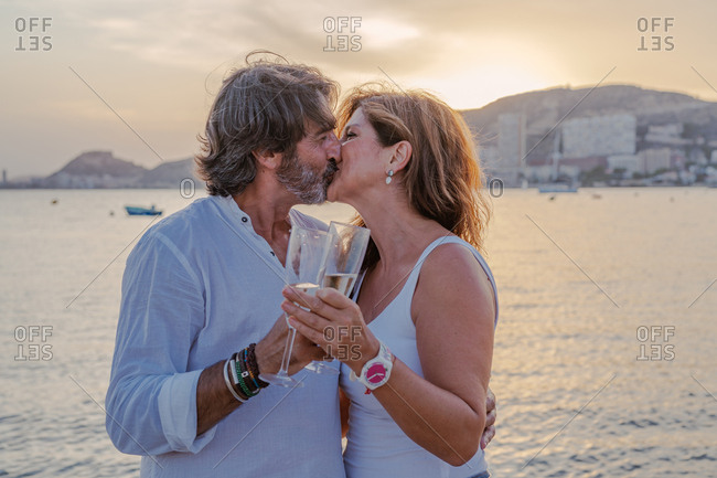 Adult bearded man hugging and kissing wife while drinking wine near sea during sunset on resort