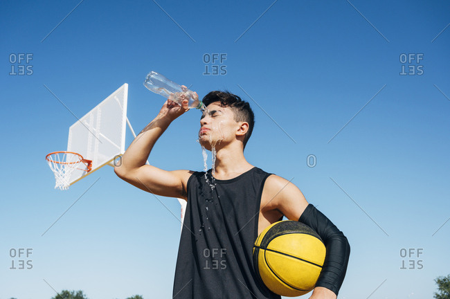 Young man standing with ball and playing on basketball court outdoor.