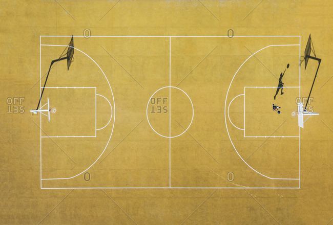 Young man playing basketball on outdoor court. Top view, bird eye view of yellow basketball court