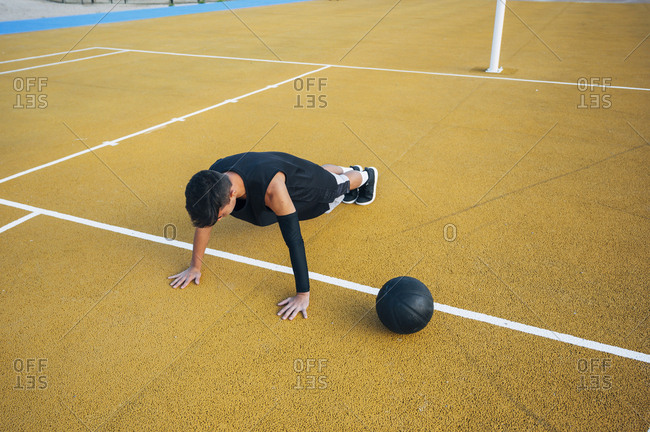 Young man playing on basketball court outdoor and doing push up