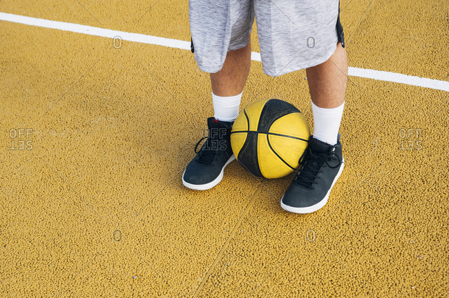 legs of crop Young man and ball playing on basketball court outdoor.