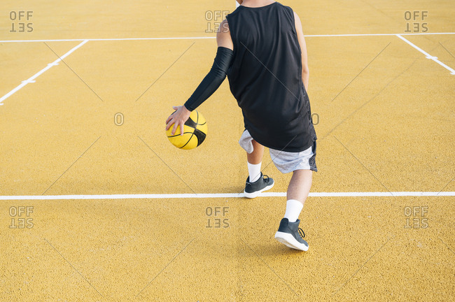 crop Young man and ball playing on basketball court outdoor fixing the