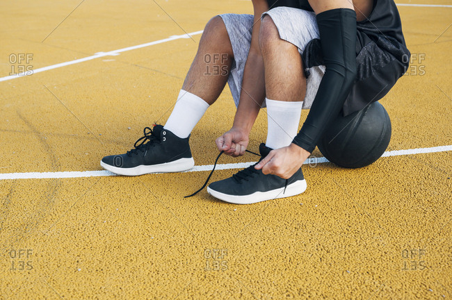 legs of crop Young man and ball sitting on basketball court outdoor fixing his sock