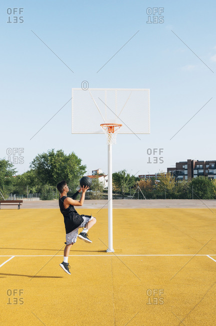Young man playing on yellow basketball court outdoor.