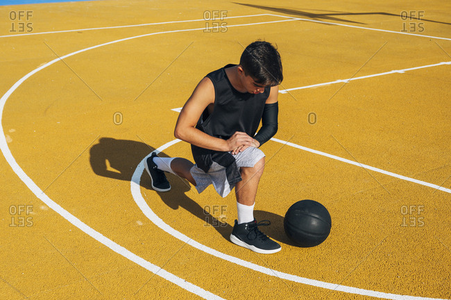 Young man and ball stretching on basketball court outdoor resting after playing basketball