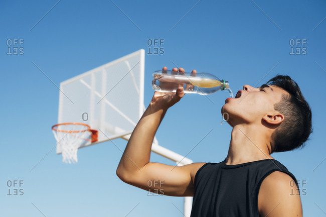 Young man playing on basketball court outdoor drinking water