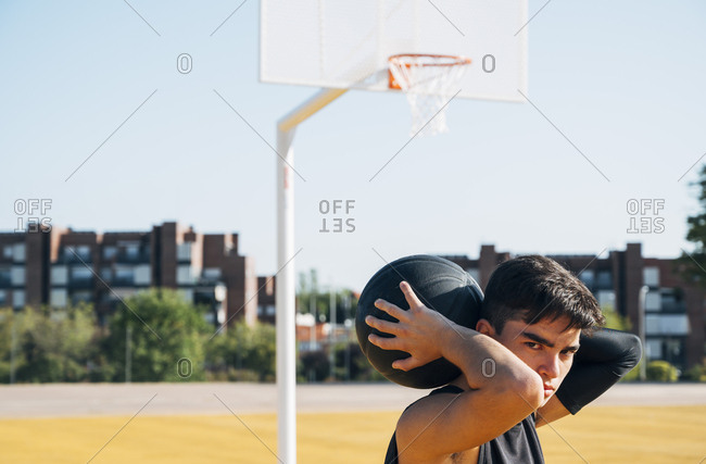 Young man playing on basketball court outdoor.