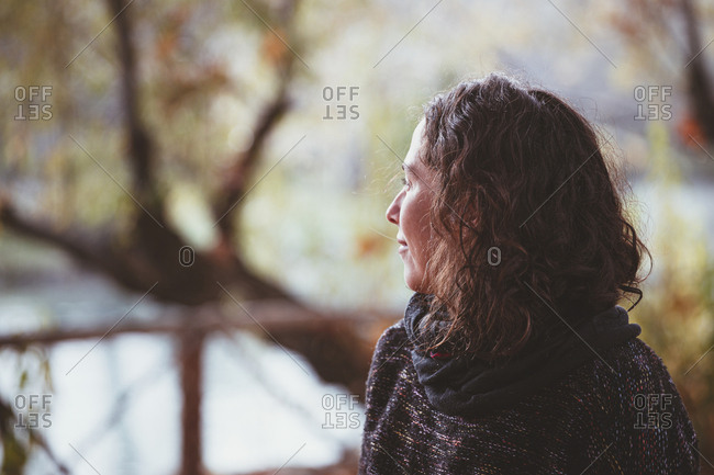 Adult lady with curly hair looking away and thinking while standing on blurred background of peaceful autumn park