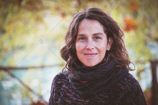 Adult lady with curly hair looking at camera and thinking while standing on blurred background of peaceful autumn park