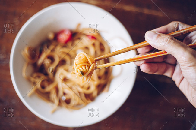 From above soft focus of crop person holding shrimp by wooden chopsticks while enjoying noodles on blurred background