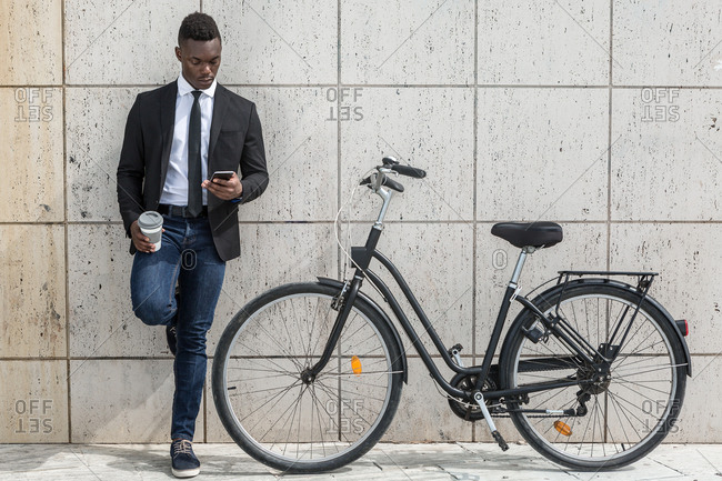 Cheerful optimistic African American guy using a mobile phone and holding coffee to go while leaning on gray tiled wall during break from cycling