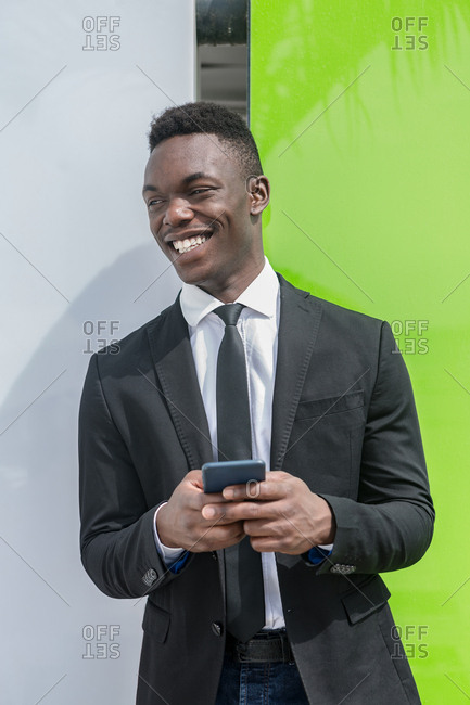 Black manager in suit messaging on cellphone while leaning on street glass window