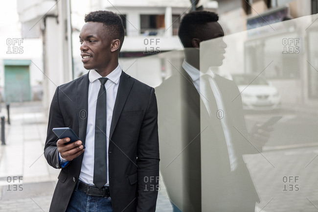Black manager in suit messaging on cellphone while leaning on street glass window with reflection