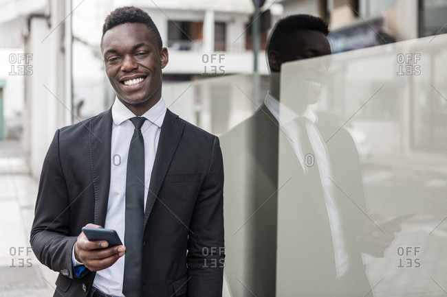 Stylish happy positive smiling black manager in suit messaging on cellphone while leaning on street glass window with reflection looking at camera