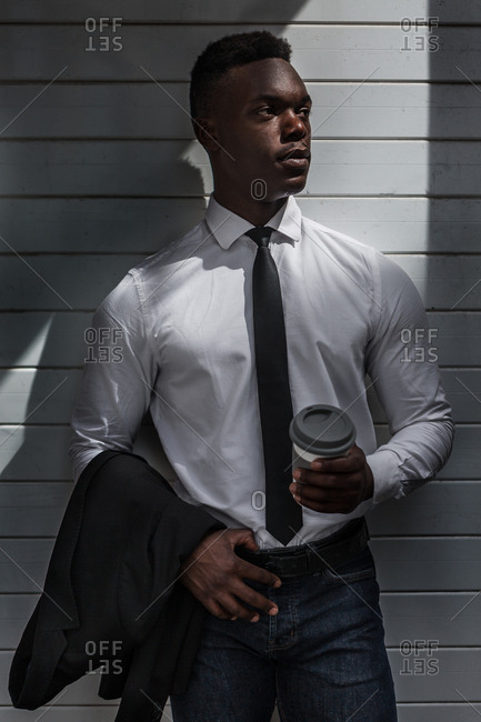 pensive tired inactive black businessman standing in shade with coffee to go and suit jacket in hands on gray striped wall looking away