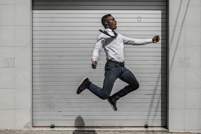 African American excited joyful screaming male jumping high for celebrating success beside street gray striped wall