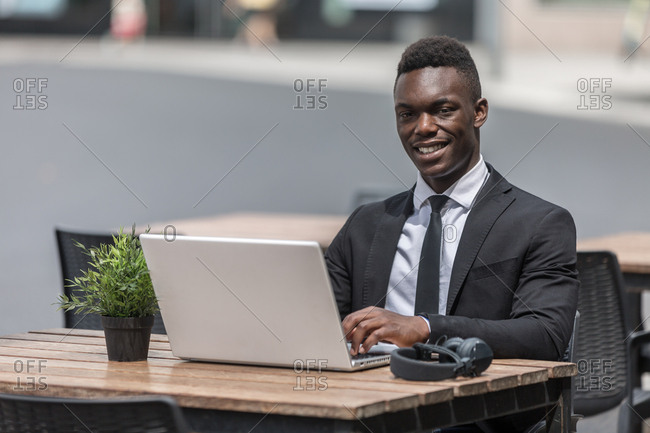 black man in suit sitting in cafe outside with laptop and in wired headphones