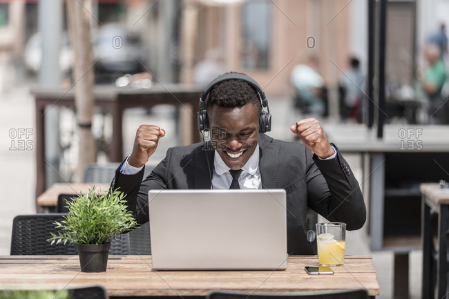 Happy joyful black man in suit rejoicing at success with raised hands sitting in cafe outside with laptop and in wired headphones