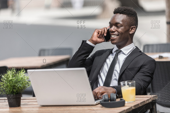African American pleased smiling handsome freelancer speaking on phone while working on laptop in urban cafeteria looking away