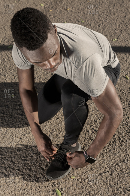 From above crouched adult African American runner with smart watch in gray shirt and black pants tying shoelaces on road