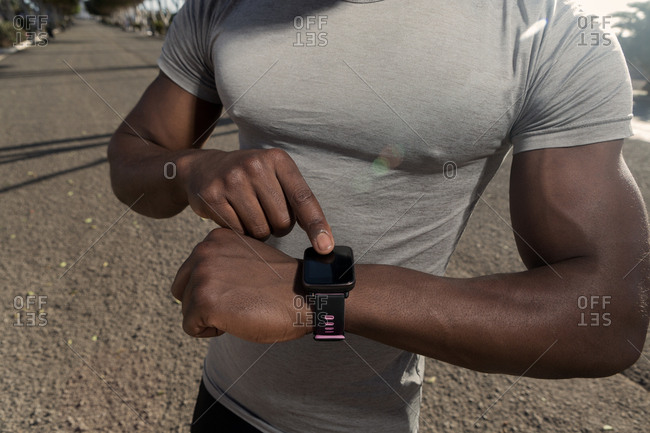 Crop muscular adult African American runner in gray shirt interacting with smart watch while standing alone on road during daytime