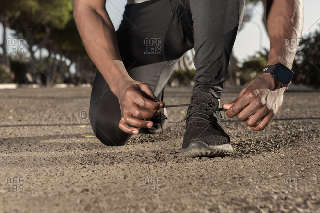 Ethnic sportsman preparing for running