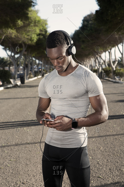 Pensive adult African American runner in sportswear and headphones focusing on screen and interacting with smartphone while standing on road during sunny day
