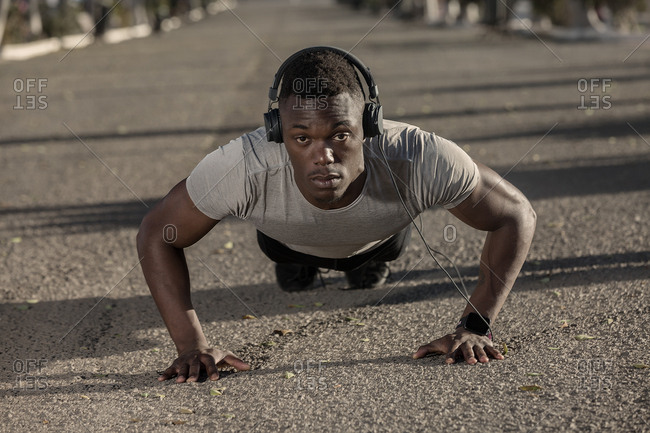 Adult African American runner in sportswear and headphones looking at camera while pushing up on road before running during sunny day on blurred background