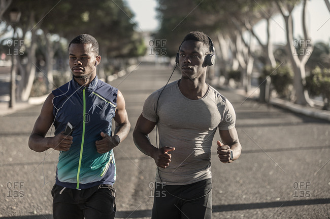 Confident adult African American runners in sportswear and headphones running and looking away on street during sunny day on blurred background