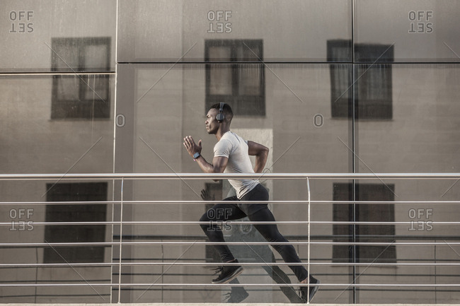 Ethnic sportsman in headphones with running near building