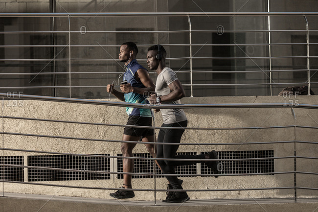 Side view of pensive adult African American men in sportswear and headphones running on walkway and looking away near building during sunny day