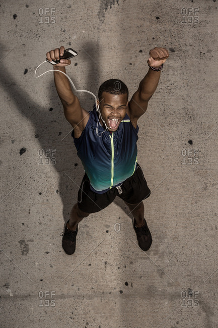 From above happy adult African American athlete in sportswear and headphones with closed eyes standing and raising arms while celebrating victory and screaming on background of gray stone floor
