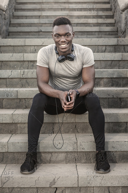 Cheerful adult African American sportsman in gray and black sportswear with headphones on neck holding smartphone and looking at camera while sitting on stone stairs