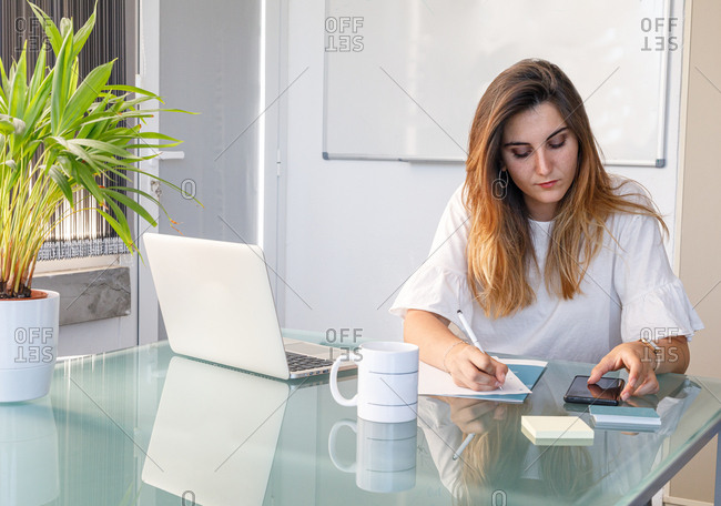 Young serious woman sitting at glass table with laptop and white mug using smartphone and taking notes on workplace