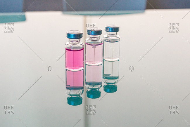 Row of transparent flasks with pink liquid reflected in glass table in biological laboratory on daytime