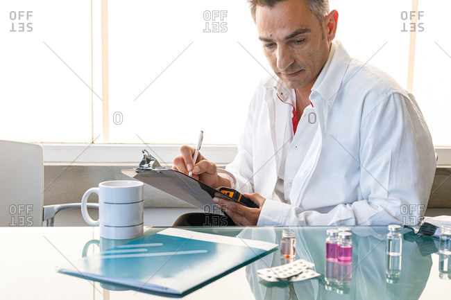 Laboratory assistant sitting at glass table with samples and pills taking notes on clipboard and looking down