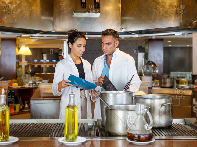 Pensive adult woman in white coat holding papers and showing information for senior male colleague while controlling food quality in canteen kitchen near big saucepans