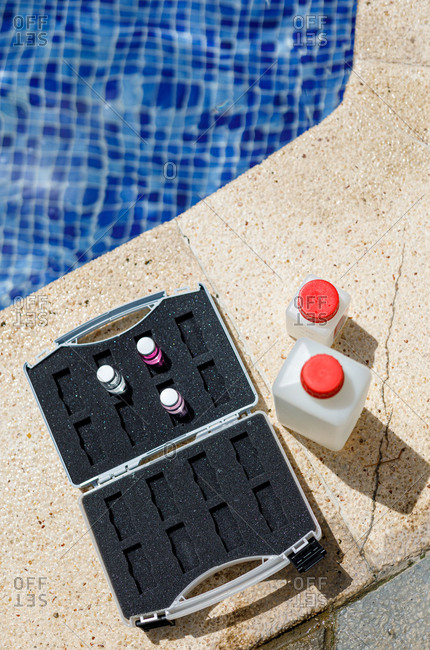From above bottles with water samples and briefcase with chemicals placed near swimming pool during safety inspection on resort