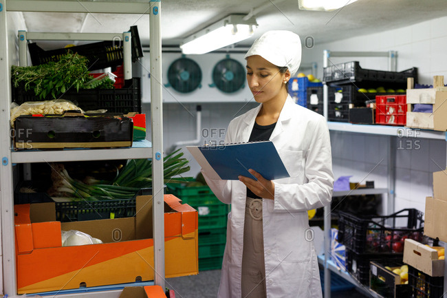 Woman in lab coat and hat making notes while checking food inside cold storage room in cafe