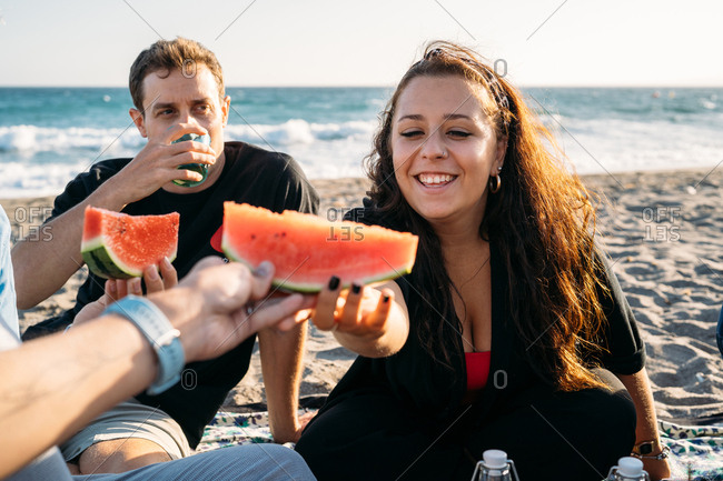 Smiling woman gives a piece of watermelon to her friend with her friend who drinks orange juice on the beach